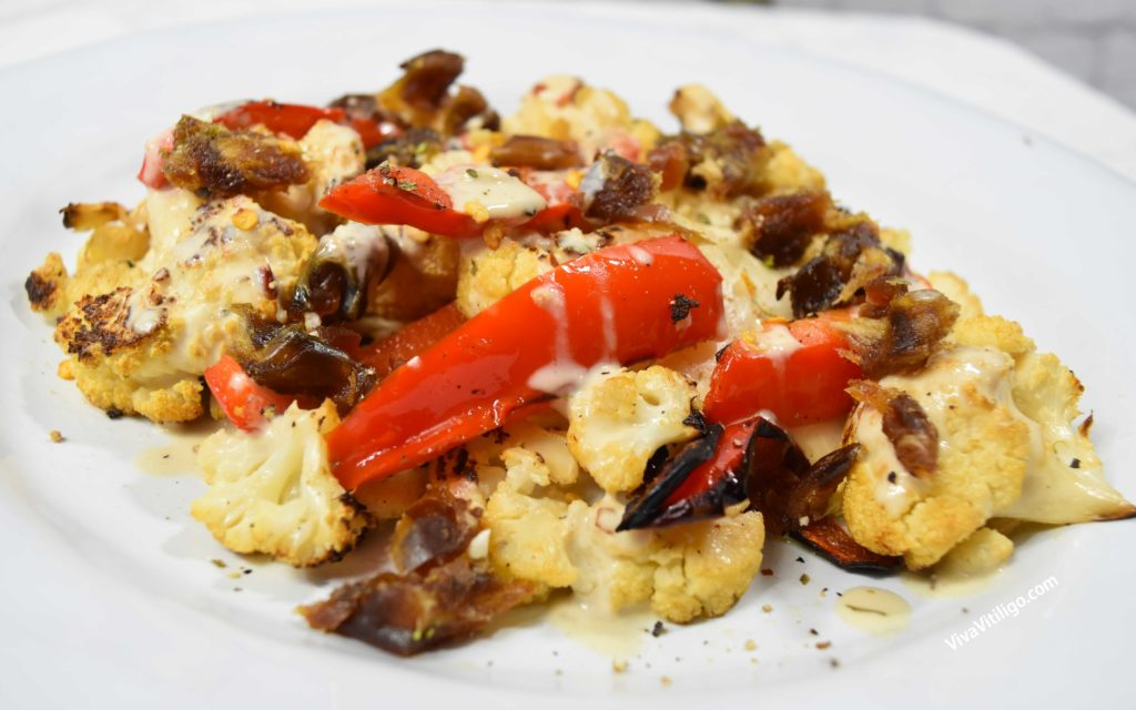 Picture of charred paleo cauliflower recipe with harissa tahini, red peppers and dates.